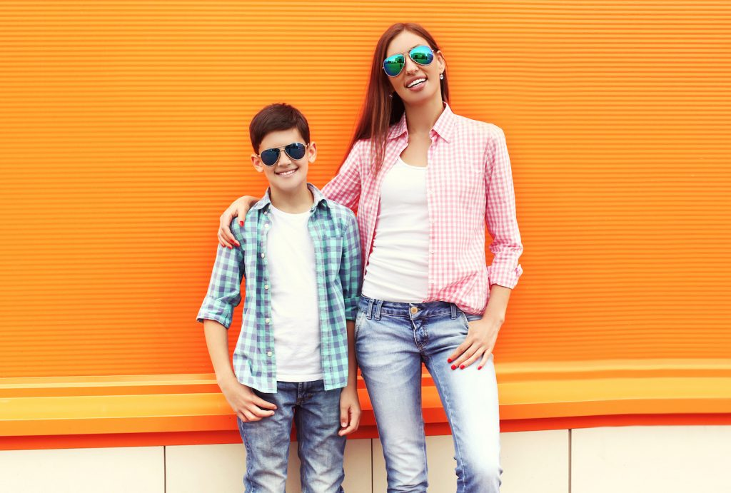 Happy mother and son teenager wearing a checkered shirt and sunglasses in city over orange background